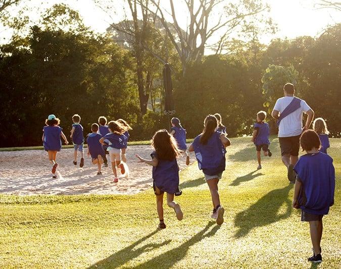 a imagem mostra um grupo de crianças e um adulto correndo em um gramado.