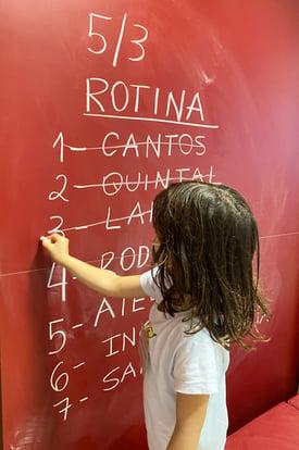 Criança em processo de alfabetização escrevendo na lousa.<br />