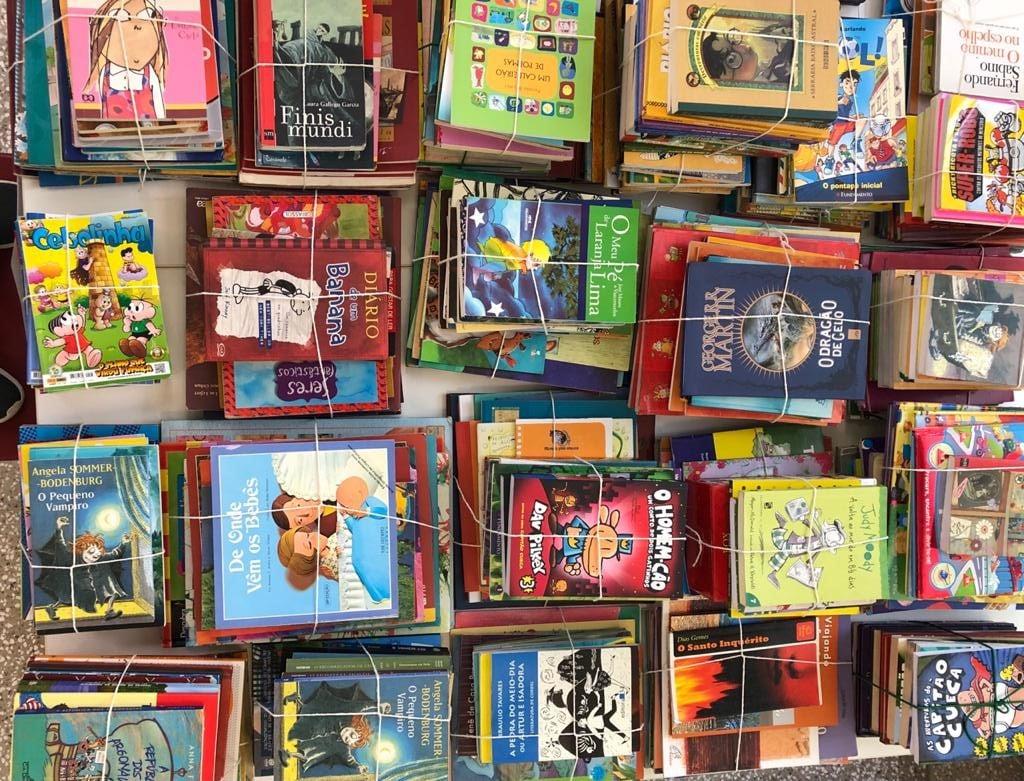 A foto contém a imagem de várias pilhas de livros amarradas com barbante. Reviva Rede Solidária - Responsabilidade social na Escola Viva