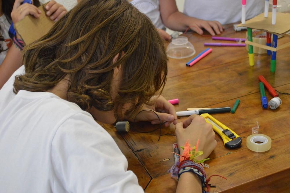 Estudante manuseando um cabo preto sobre uma mesa. Ao redor, estilete, canetas coloridas, durex., demonstrando a importância da cultura maker para a educação.