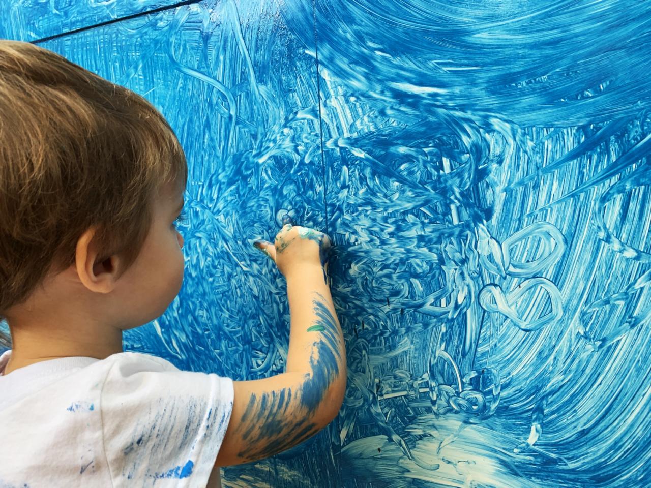 Criança pintando com dedo com tinta azul em uma parede já pintada de azul.