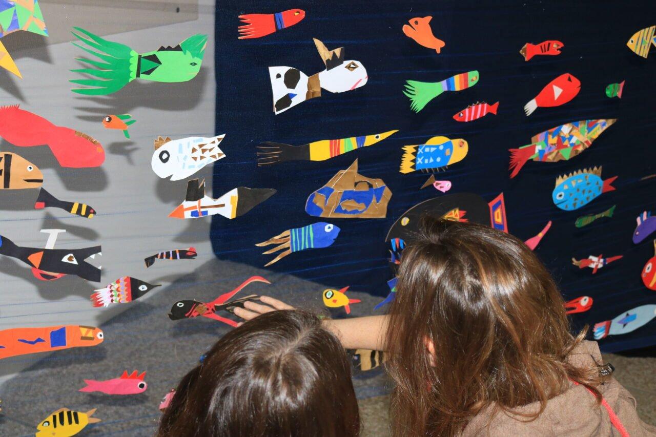 crianças juntas observam peixes de papel