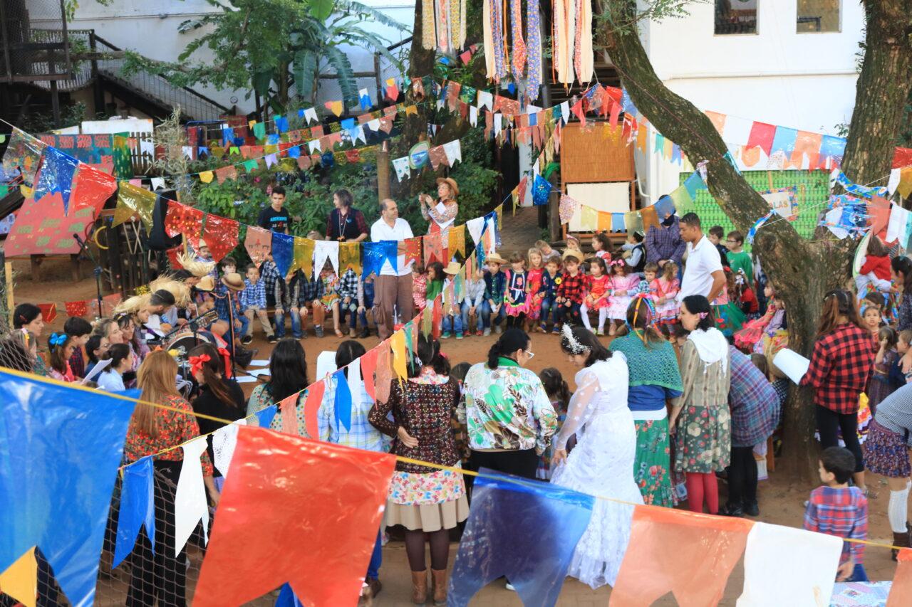 Pessoas dançam em roda na Festa Junina da Educação Infantil da Escola Viva em 2019