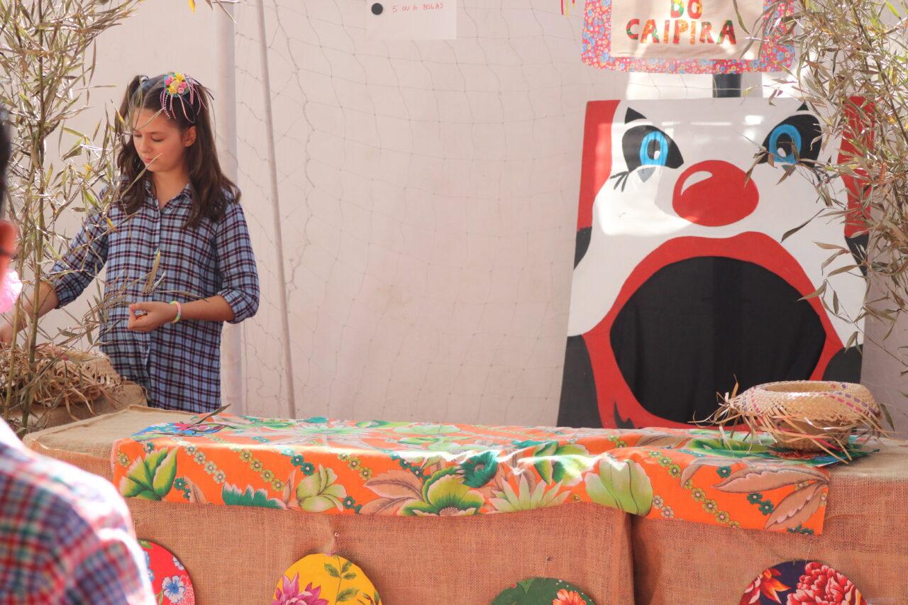 menina ao lado da boca do palhaço, brincadeira de festa junina