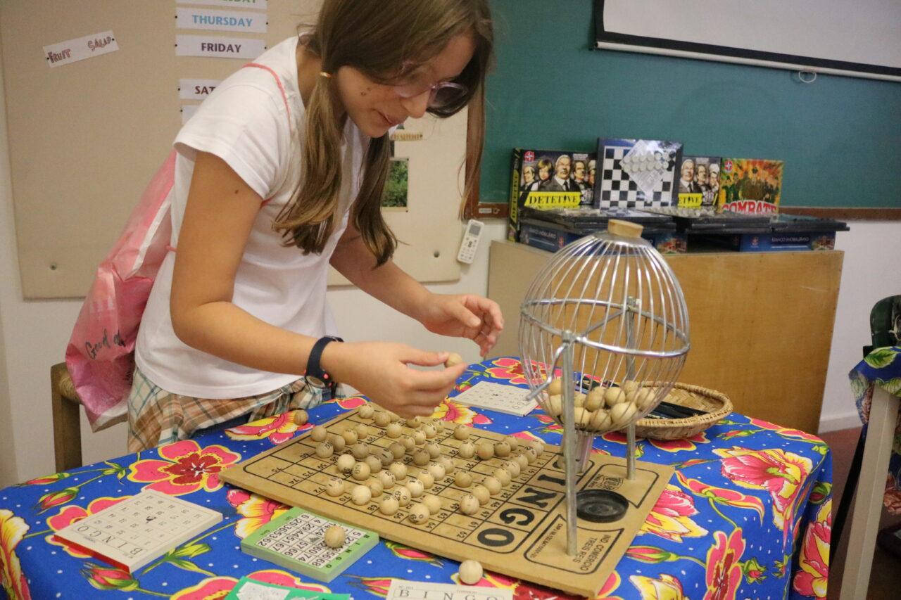 Menina sorteando números do bingo durante festa junina da escola viva