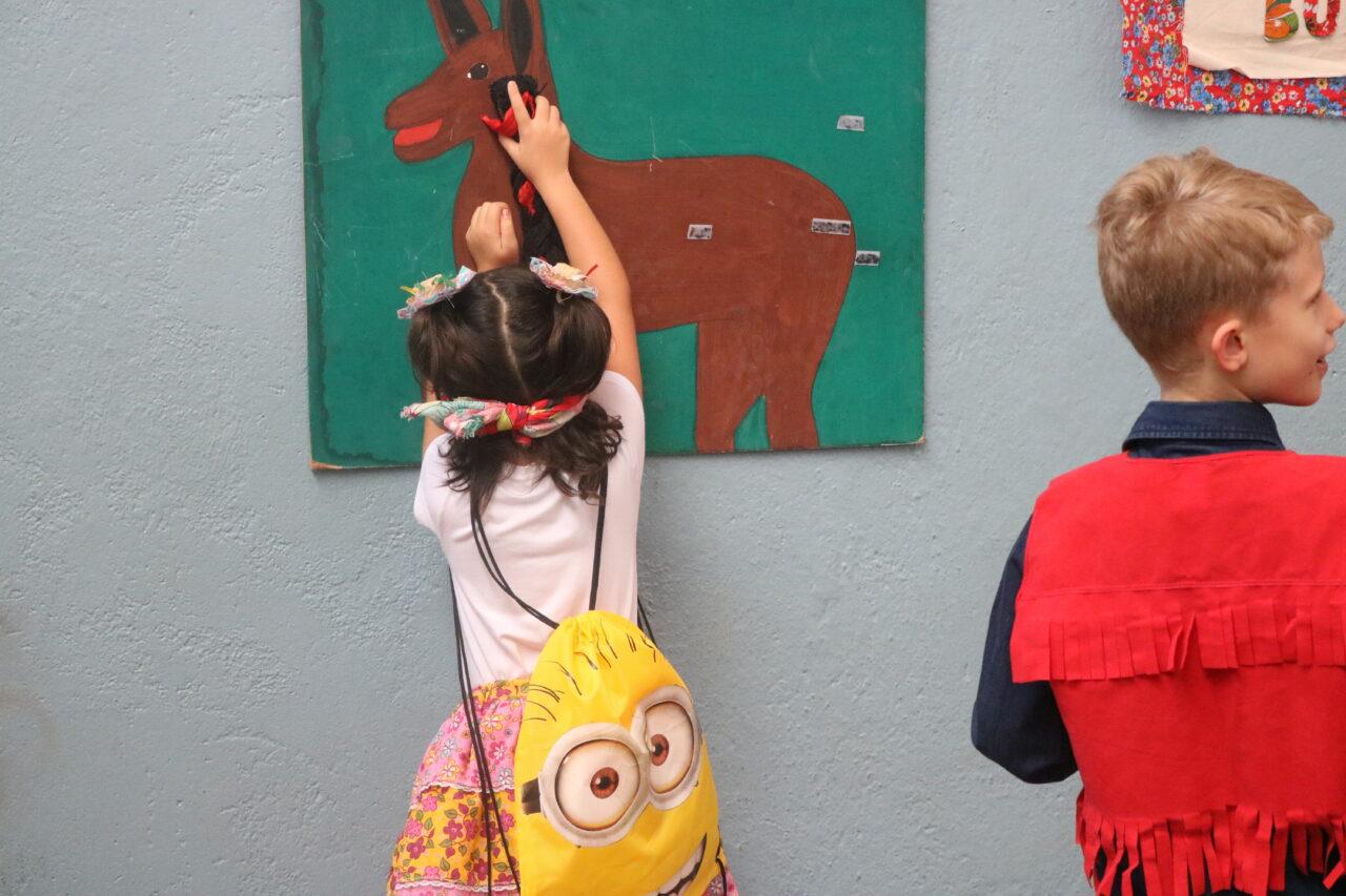 Menina de olhos vendados, tentando acertar o rabo no burro, brincadeira típica de festa junina