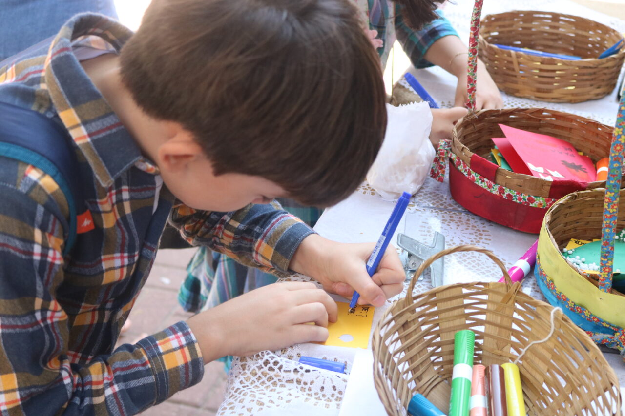 Menino preenchendo correio elegante na festa junina da escola viva