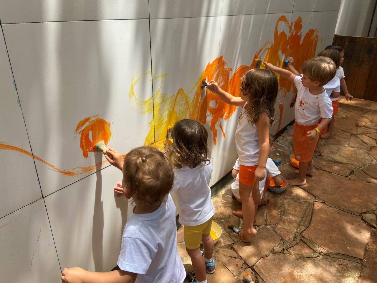 Crianças pequenas pintando a parede com as cores amarela e laranja.